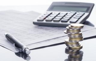 Schreibtisch mit Taschenrechner, Geld und Stift