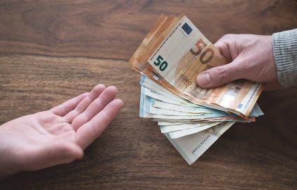 hand of one person handing over cash to another